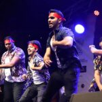 A team of male Bollywood dancers in the thick of their performance_